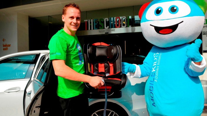 Mercedes-Benz Malaysia vice president (Passenger Cars) Mark Raine with 'MobileKids' ambassador Moki during the start of the company's child seat campaign.