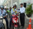 Perodua president & CEO Datuk Aminar Rashid Salleh (right) handing out safety vests and leaflets to motorists during the flag off ceremony.