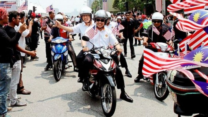 Ahmad Zahid and Liow riding a motorcycle at the closing ceremony of a nationwide programme where 5,000 members of the voluntary 1JPJ Young Squad will be riding around the country.