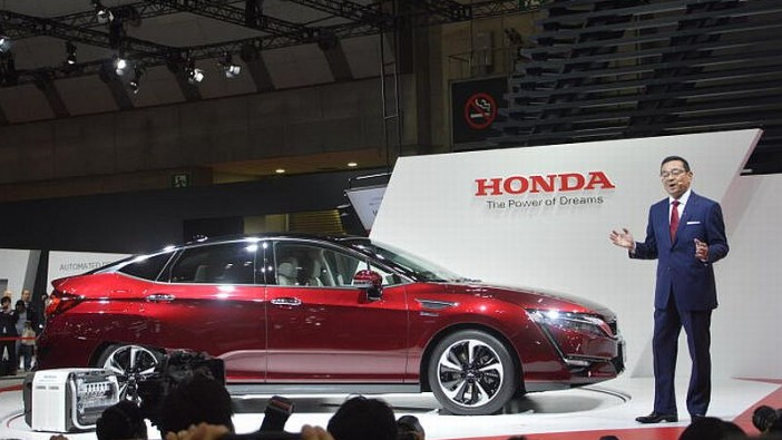 Honda Motor Co Ltd president and CEO Takahiro Hachigo with the hydrogen-powered Clarity FCV (fuel cell vehicle) at the 2015 Tokyo Motor Show.